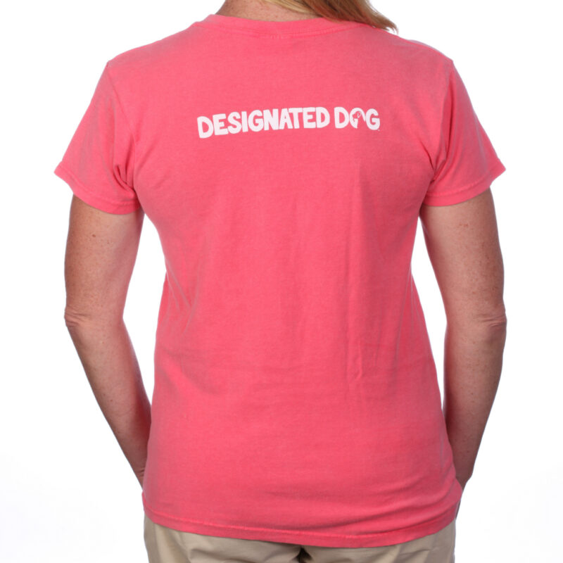 Back of lady wearing Designated Dog V-neck logo tee in coral.